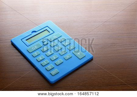 A Blue Calculator on a Wooden Background