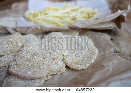 preparing breaded veal cutlet with french fries