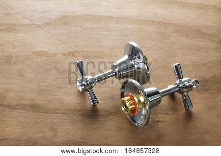 Two Silver Taps on a Wooden Background