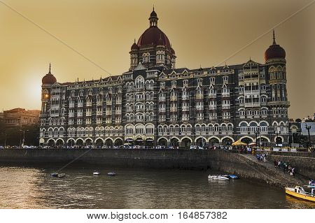 MUMBAI, INDIA - NOVEMBER 12, 2016: A view of the Taj Palace at sunset looking over part of the harbor in front of the promenade in Mumbai, India.
