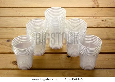 Stacks of Plastic Cups on Wooden Background