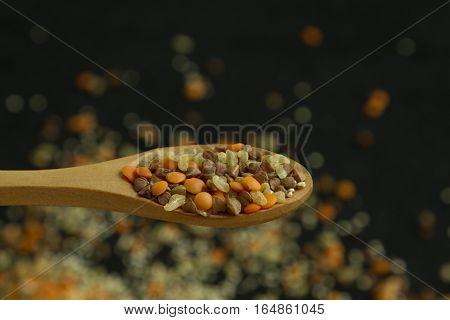 Spoon with four different groats: buckwheat lentil quinoa bulgur on black background
