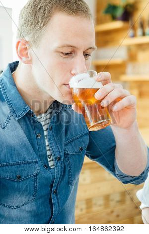 Adult blond man tasting light beer on a beer tasting