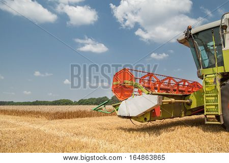 combine harvester on a wheat field with a cloudy sky