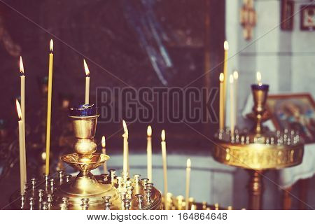 Lighting yellow candles in Orthodox Church Russia