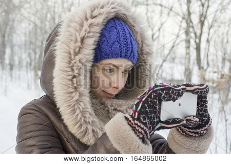Young female photographer wearing winter clothes taking pictures on a mobile device outdoor shot