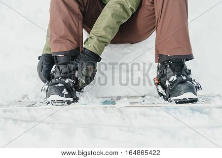 Unrecognizable young man putting on his snowboard and tightening the straps on background of snow in winter