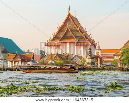 Chao Phraya River and Wat Arun Temple at sunrise. Thai traditional boat and ancient temple in sunrise light. Bangkok, Thailand