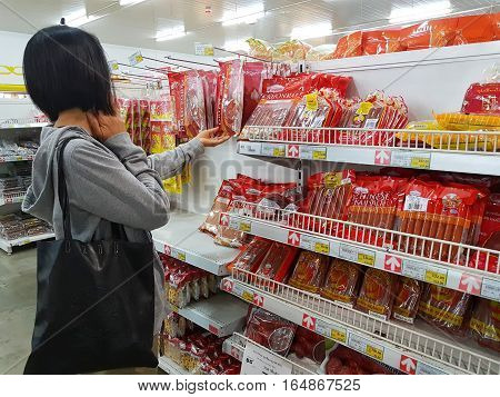 CHIANG RAI THAILAND - NOVEMBER 29 : unidentified woman buying sausage in packaging for sale on supermarket stand or shelf on November 29 2016 in Chiang rai Thailand.