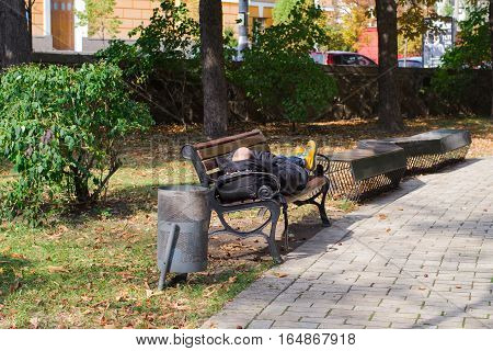 adult man with a bald head sleeping on a bench in summer city park