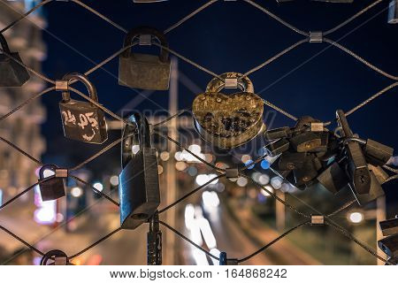 Locks on a metal wire fence with city light in the background