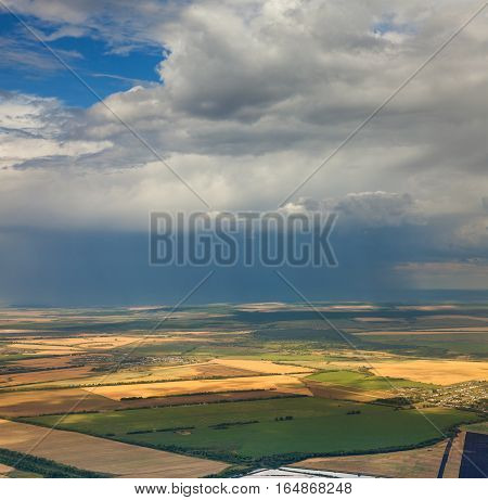 Aerial view of countryside with fields of crops and thundercloud in the summer.