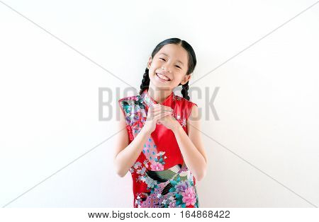 Little oriental children wishing you a happy Chinese New Year in traditional dress (Cheongsam) with beautiful smile standing on white background.