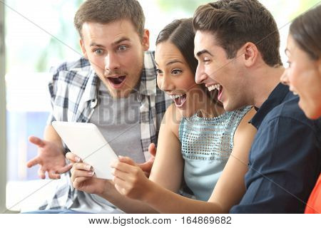 Four amazed friends watching media content together in a tablet sitting on a sofa in the living room at home