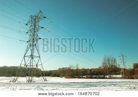 Power transmission line on a background of a winter landscape. Toned photo