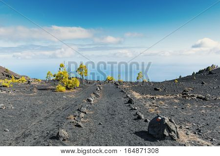 """Shot of the famous trekking path """"Ruta de los vulcanos"""" taken in the south of la Palma nearby Los Canarios. The photo shows a volcanic rock trail which seems to end right in the atlantic ocean."""