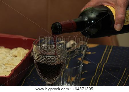 A man pouring glass of red wine