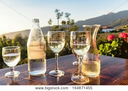 Picturesque white wine cover with a bottle of water standing on a table of a restaurant terrace in La Palma canarian islands. The sun reflects in the condensed glass of the cover.The scenic place is surrounded by a quaint canarian garden and mountains.