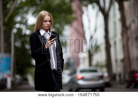 Girl on city street calling on the phone. She holds phone and dials number.