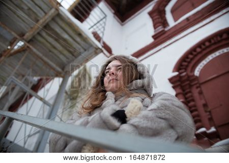 walk around the city: the girl's portrait in a gray short fur coat who stands behind a handrail and looks in a distance in the winter