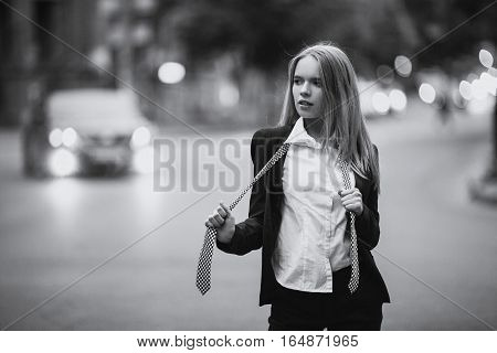 Girl on city street in shirt and tie. She has loose hair and loosened her tie.