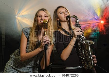 Attractive women playing on saxophone and with microphone at music concert