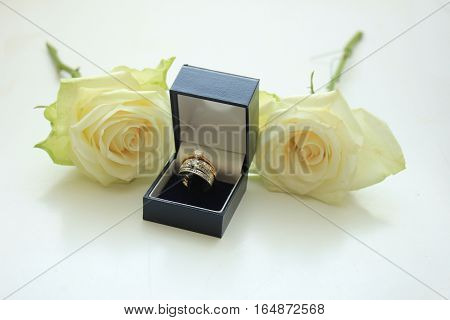 Engagement rings in boxes and white rose