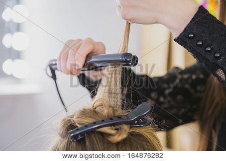 Close up of stylist hands with styling iron straightening woman hair at salon