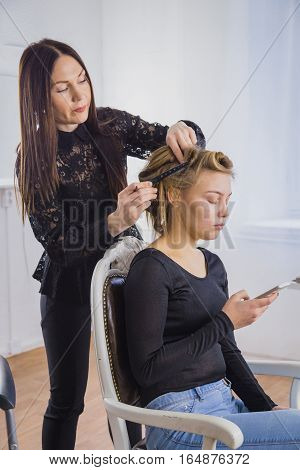 Professional hairdresser, stylist combing hair of female client in white make up room. Beauty and haircare concept