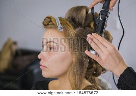 Professional hairdresser, stylist making curls in white make up room. Beauty and haircare concept poster