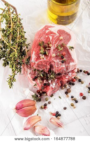 lamb chop with fresh thyme spices garlic and a bottle of sunflower oil