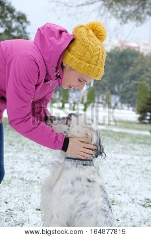 young woman in winter clothes caress a big white dog in a snowy park