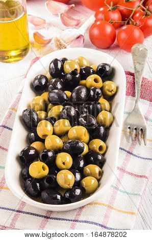 white bowl with oily green and black olives tomato background garlic and a bottle of olive oil on a kitchen towel