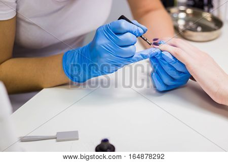 Professional beautician applying nail polish to female nail in a nail salon.