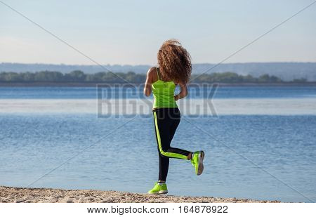 Young, Beautiful, Athletic Woman With Long Curly Hair In The Morning Runs On The Beach, By The Lake.