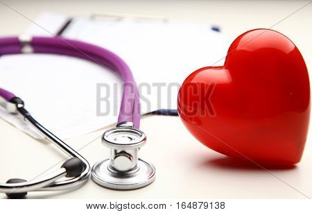 A heart with a stethoscope isolated on wooden background