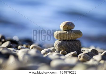 Zen balancing pebbles on the blue beach