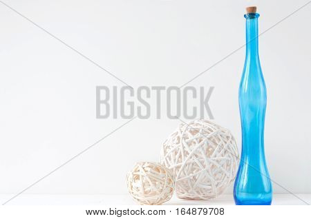 Minimal elegant composition with rattan balls and blue bottle for blogs, shops and social media