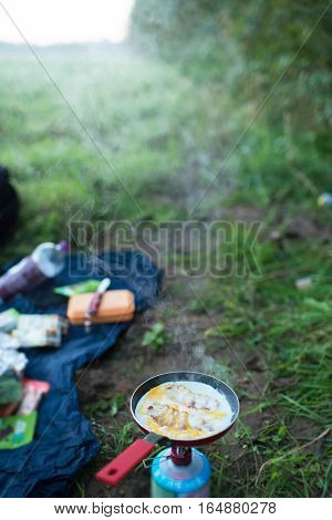 Frying Egg With Bacon On Camp Gas In The Field. Hiking Trip.