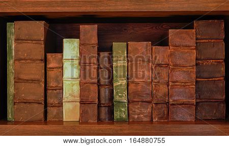 Antique books on old wooden shelf. Shelf with old books.
