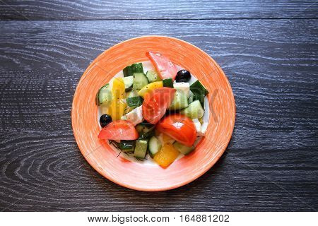Appetizer for dinner. Plate with salad on dark wooden background