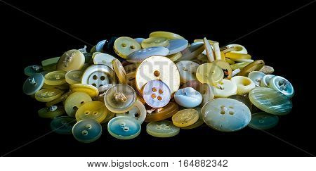 A bunch of old plastic buttons on black background