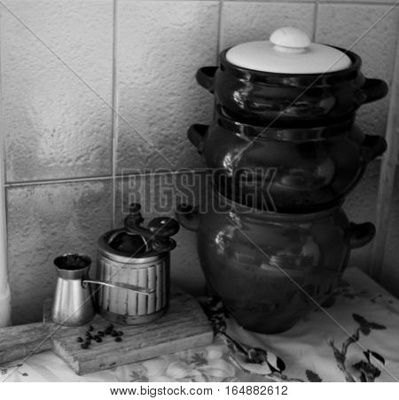 Vintage side view of coffee, pepper or sugar grinder or mill with a mechanical rustic handle and metal turka  on wooden board in black and white style