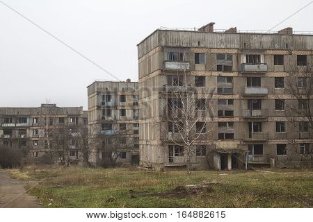 Three abandoned apartment houses without windows and overgrown with a grass in a ghost-town in Ukraine