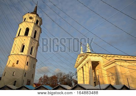 VILNIUS, LITHUANIA: The Belfry (Cathedral Clock Tower) and the Cathedral at Cathedral Square with the roofs of Christmas market stalls in the foreground