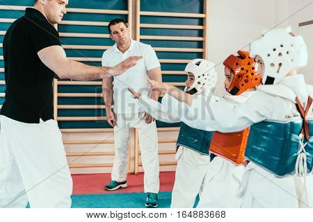 Tae kwon do instructors working with children on class