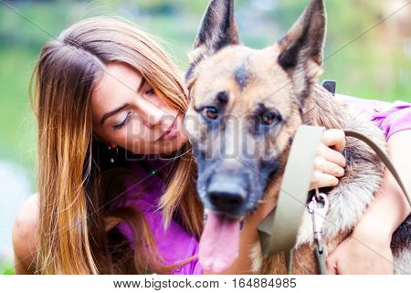 Happy woman kisses her shepherd. Beautiful girl and the dog.