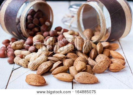 Hazelnuts almonds and peanuts scattered from the jars on a wooden table.