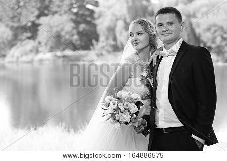 Day to remember. Black and white shot of a beautiful young bride with her husband after getting married