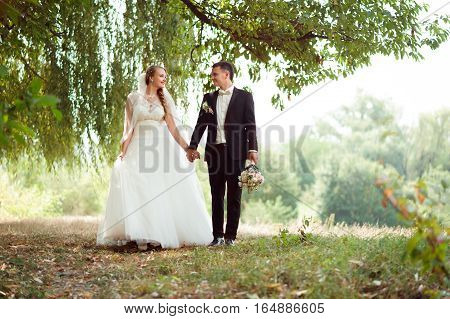 Side by side. Full length soft focus shot of a newlywed couple on the walk in the park